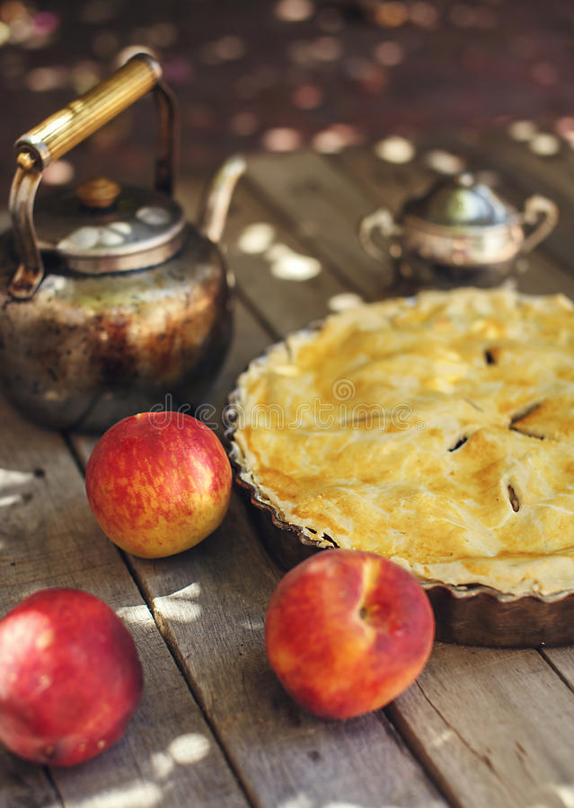 Peach pie with fresh fruits on wooden background. Delicious homemade peach pie with fresh fruits peaches and vintage kettle on old wooden table outdoors royalty free stock photography