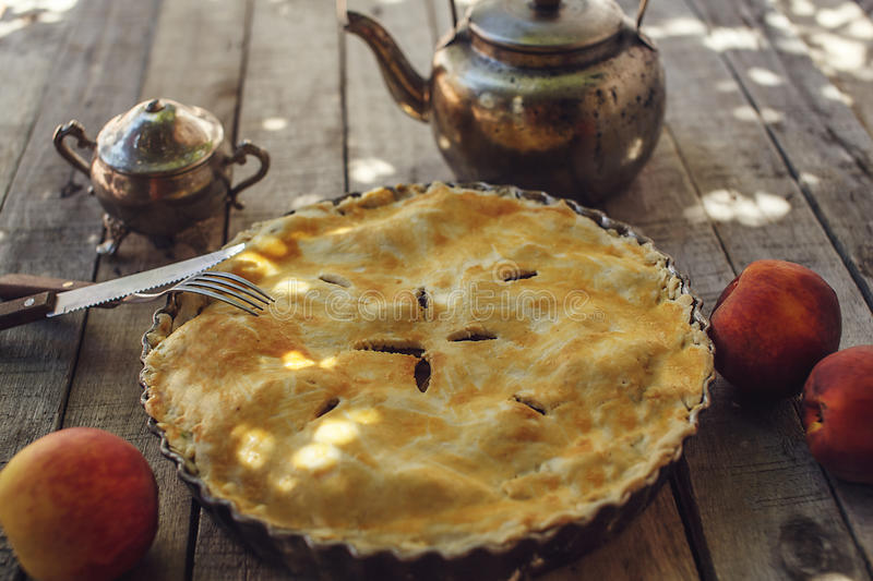 Peach pie or tart with kettle. Homemade peach pie or tart with fresh fruits with vintage kettle, fork and knife on the wooden background. Eating concept stock photography