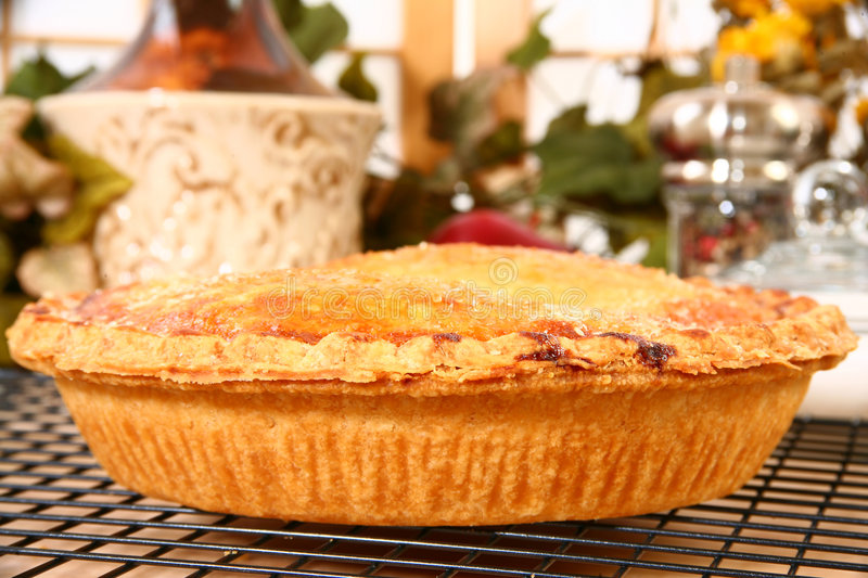 Peach Pie Treat. Close-up of a delicious golden brown peach filled pie sprinkled with sugar royalty free stock image