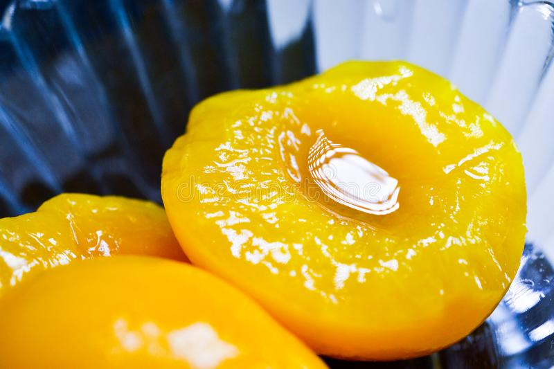 Peach slices in syrup on a glass bowl stock image