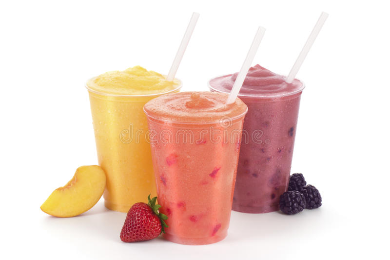 Peach, Strawberry, and Blackberry Fruit Smoothies. Three flavors of smoothies: peach, strawberry, and blackberry in generic cups with straws and fruit garnishes stock photo