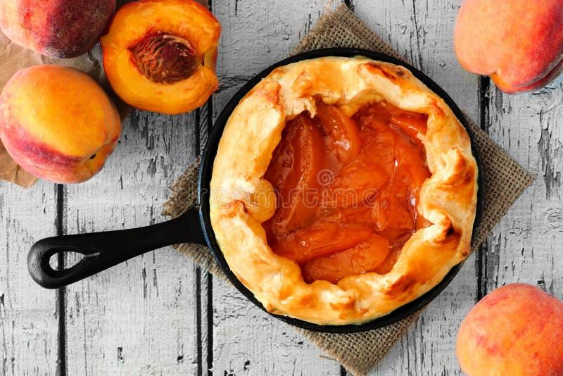 Peach tart in cast iron skillet, overhead on white wood. Rustic peach tart in cast iron baking skillet, overhead scene on white wood royalty free stock photos