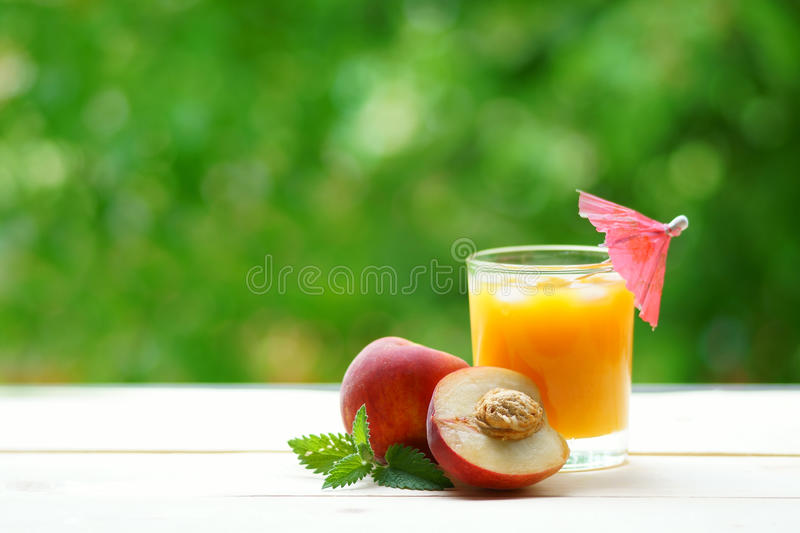 Peach whole and a half with a glass of juice. stock photo