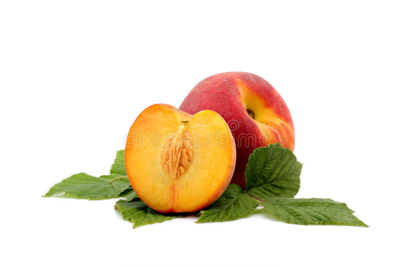 Peaches. On green leafs, isolated on a white background