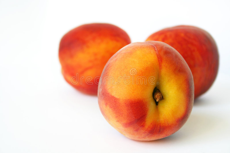 Peaches. Three tasty juicy peaches on a white background
