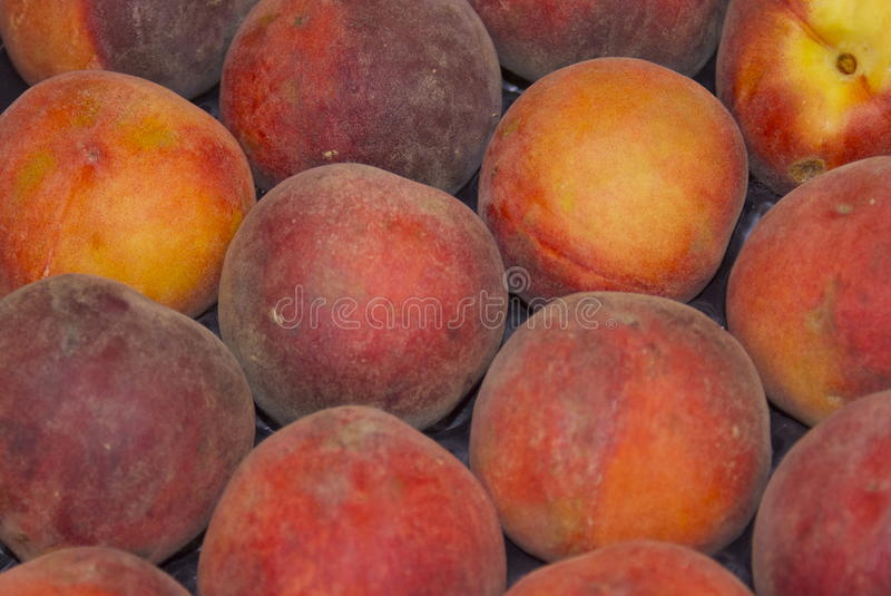 Peaches in a giant peach pile. Ripe Peaches on a market fruit and vegetable stall stock images