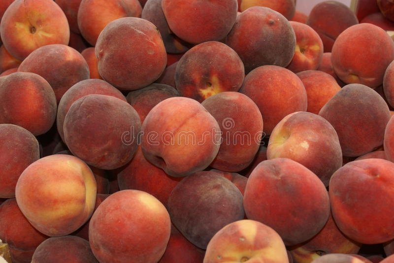 Peaches in a giant peach pile. Stack of peach fruit in a pile on an open air fruit market stall royalty free stock images