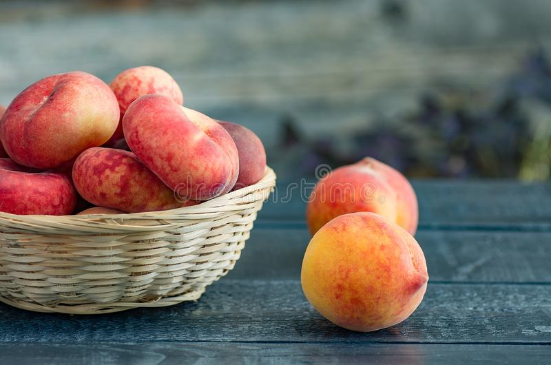 Ripe peaches in a wicker basket on a dark wooden background royalty free stock photo