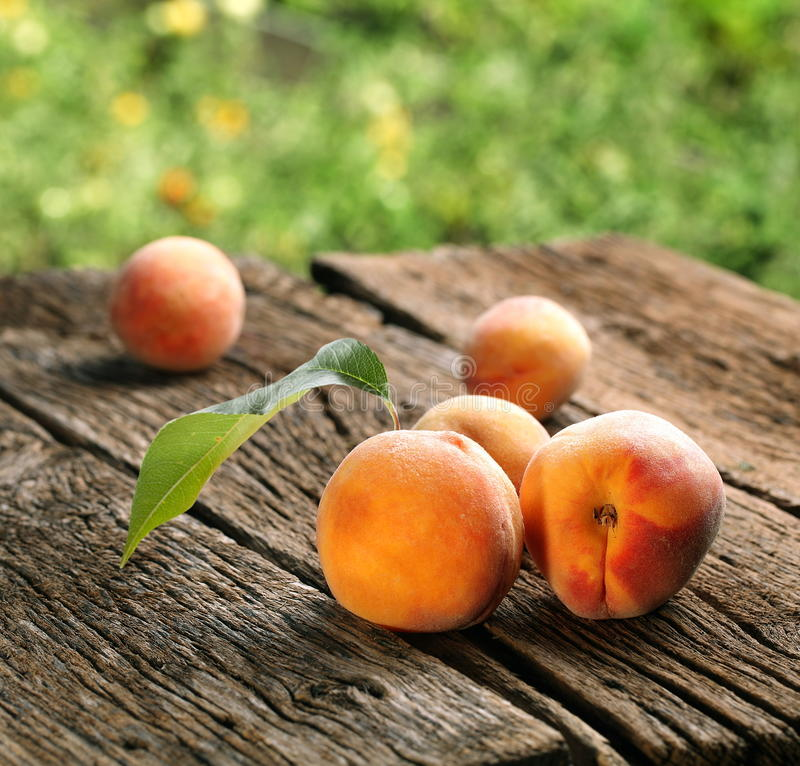 Peaches with leaves. On the old wooden table stock images