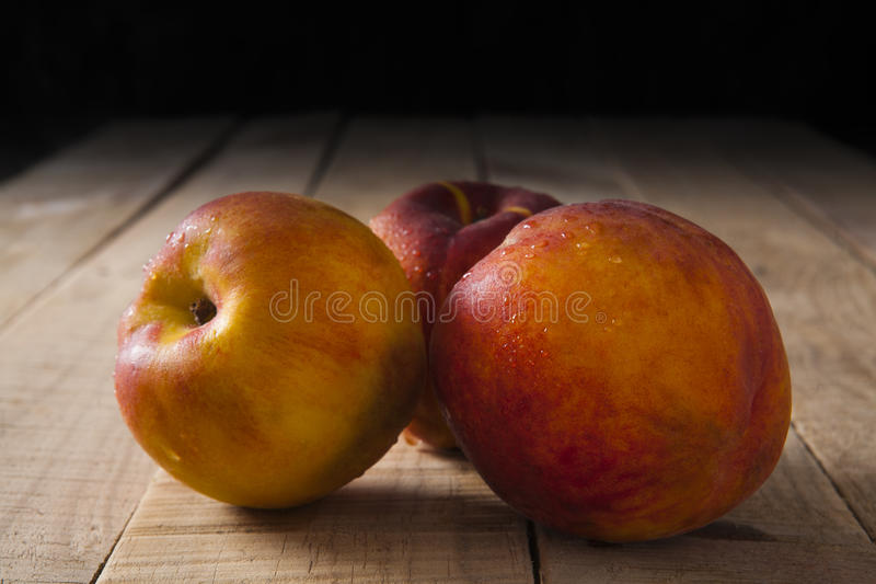 Peaches on a old wooden table royalty free stock images