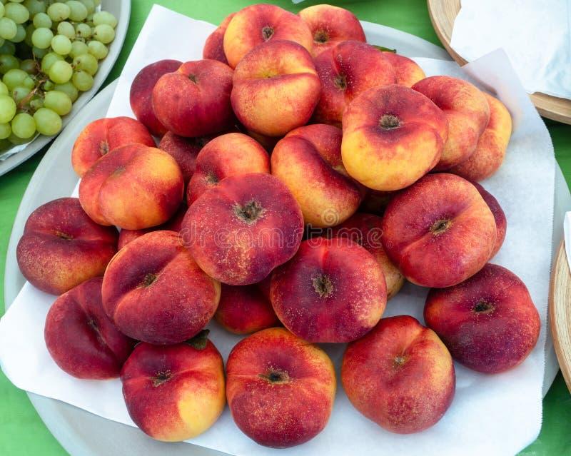 Peaches Red Yellow Stack matura su un piatto, sulla vendita, vista dalla cima fotografia stock
