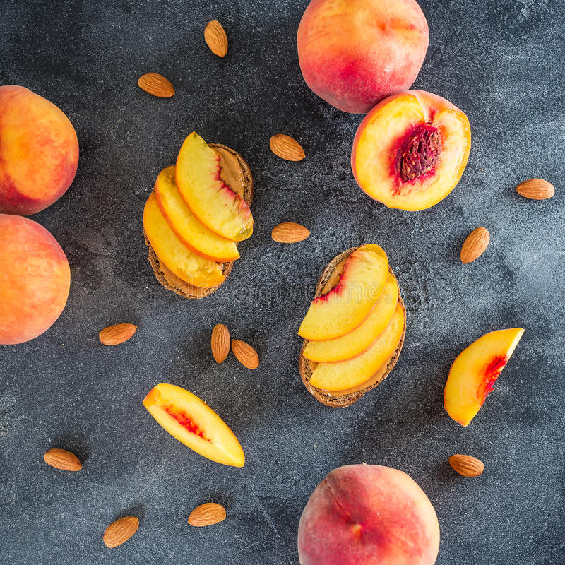 Peaches and snacks with crispbread and peanut butter on dark background. Sandwiches on dark table. Healthy food concept. Flat lay, stock photography