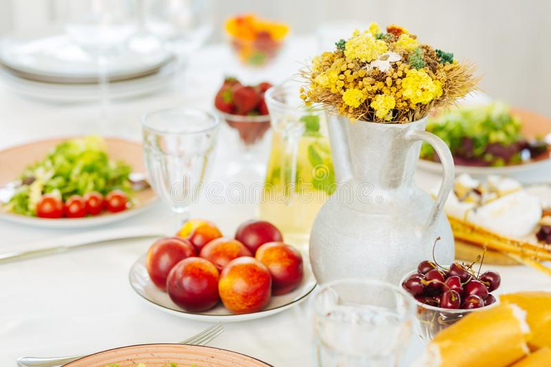 Peaches and sweet cherries lying on plates near vase with flowers stock photo