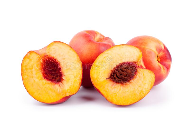 Peaches whole and cutted in halves on a white background isolated close up. Bright orange ripe peaches whole and cutted in two halves with bone inside on white royalty free stock images