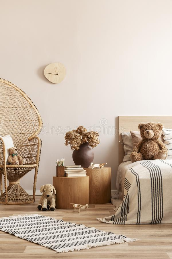 Free Peacock Chair With Pillow And Teddy Bear Next To Two Nightstands With Books And Vase With Flowers And Single Bed With Toy On It Stock Images - 155087624