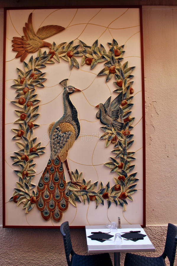 Peacock with doves ceramic wall above a restaurant table stock photo