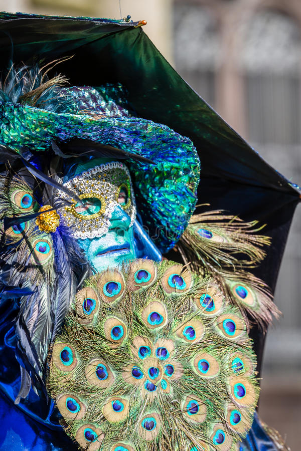 Peacock Fan. Schwaebisch-Hall, Germany - February 23, 2014 - Man, dressed up in a Venetian style costume, holding a fan made of peacock feather, attends the royalty free stock photography