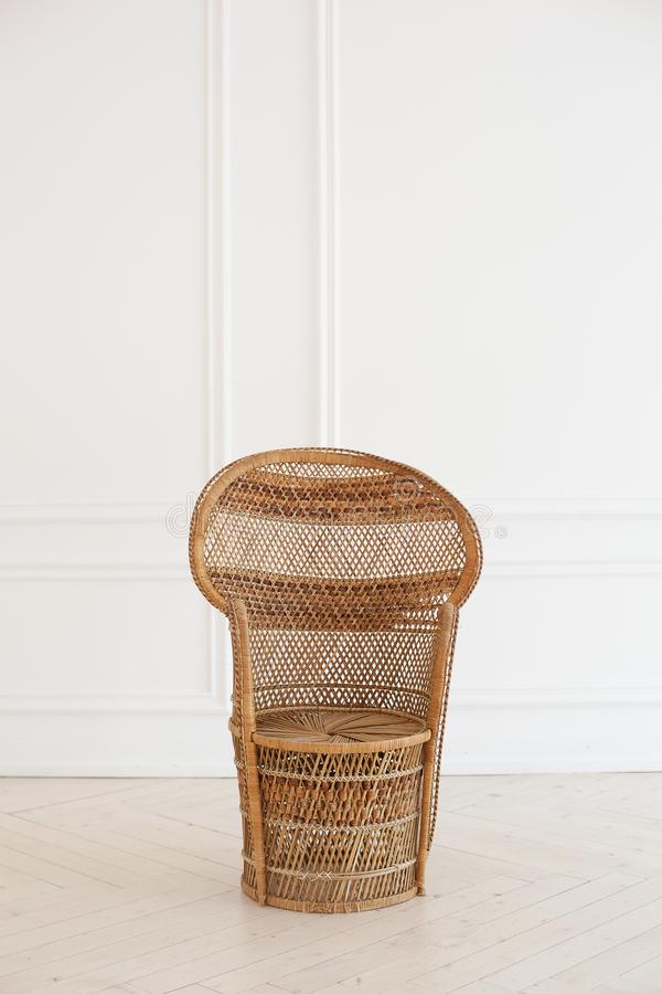 Peacock wicker chair in a spacious bedroom interior. Rattan peacock armchair by the white empty wall in the living room. Scandinav stock photography