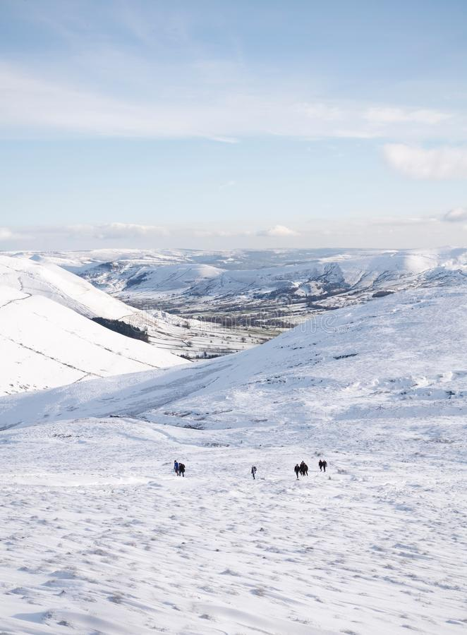 Hikers climbing Kinder Scout in snow royalty free stock images