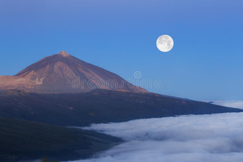 The peak of El Teide above the clouds with full moon during sunrise royalty free stock photo