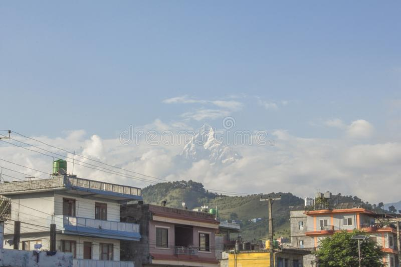 Peak of high mountain with snow sticks out of the clouds above the city stock image