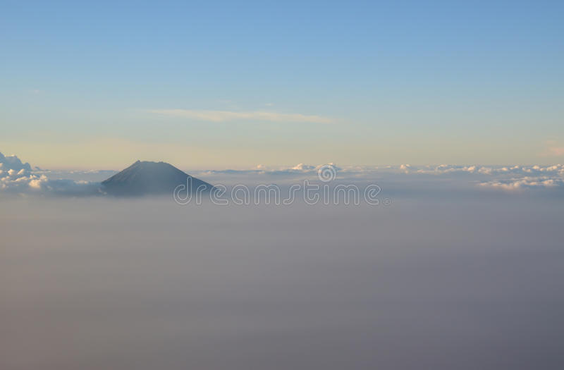 Peak of mountain visible above the clouds during sunset. Peak of mountain visible above the silky surface clouds during sunset. This picture was taken in a royalty free stock images