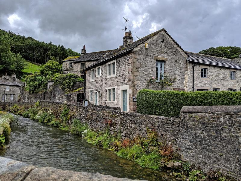 Peakshole Water running through Castleton. Stone built cottages in Castleton, Derbyshire next to the water coming down from Peaks Cavern in the Peak District stock photography