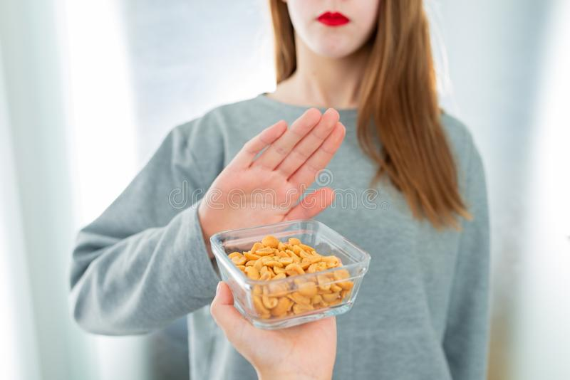 Peanut allergy concept - food intolerance. Young girl refuses to eat peanuts. Shallow depth of field royalty free stock photography