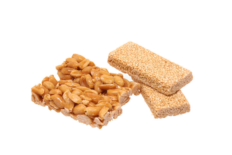 Peanut brittle with sesame seeds and peanuts. Isolated on white royalty free stock photo