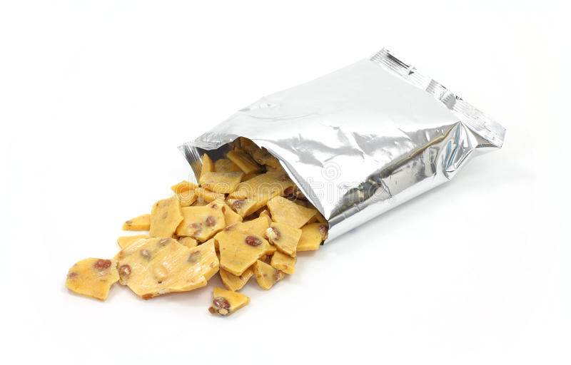 Peanut brittle spilling from bag stock photos
