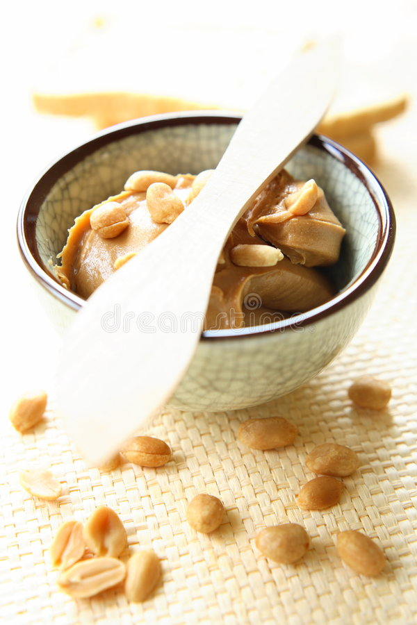 Peanut Butter. With whole nuts in glass bowl. There is excellent addition for sandwiches and desserts royalty free stock image