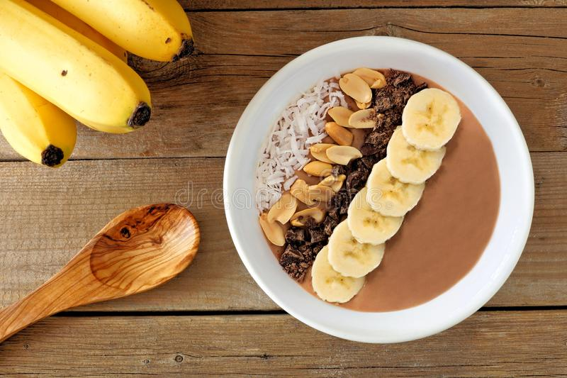 Peanut-butter, banana, chocolate smoothie bowl on rustic wood royalty free stock photography