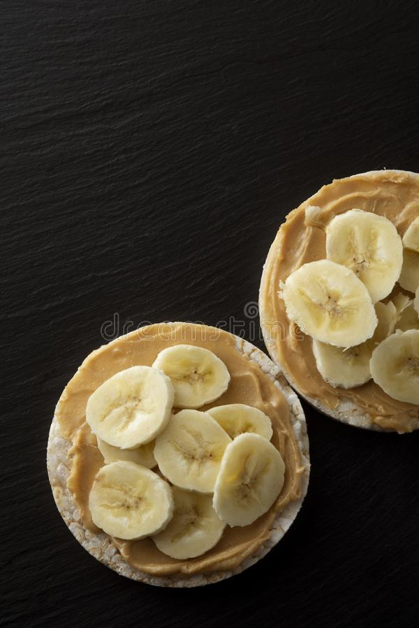 Peanut butter and banana on rice cakes, healthy, dietary food. Black background. Peanut butter and banana on rice cakes healthy, dietary food. Black background stock photo