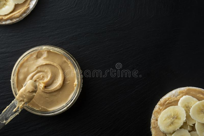 Peanut butter and banana on rice cakes, healthy, dietary food. Black background stock photography