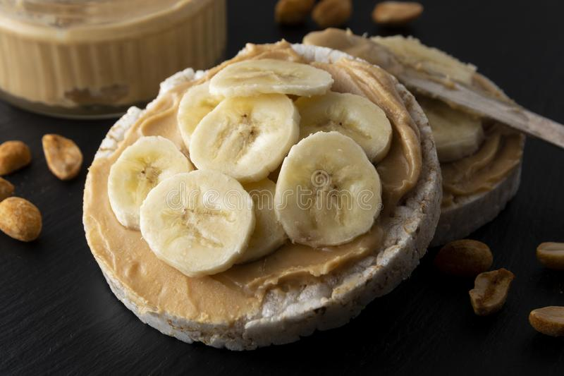 Peanut butter and banana on rice cakes, healthy, dietary food. Black background royalty free stock photo