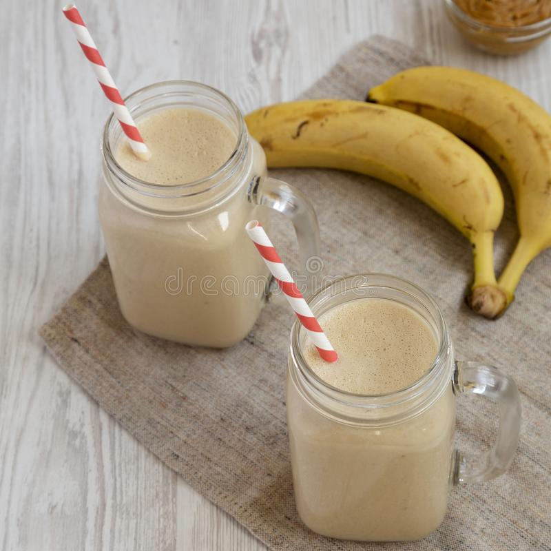 Peanut butter banana smoothie in glass jars on a white wooden surface, low angle view. Closeup.  royalty free stock photos