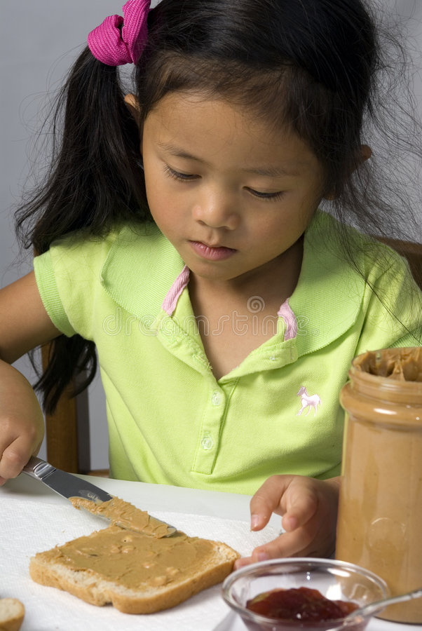 Peanut Butter and Jelly 1. A young child makes a peanut butter and Jelly sandwich royalty free stock image