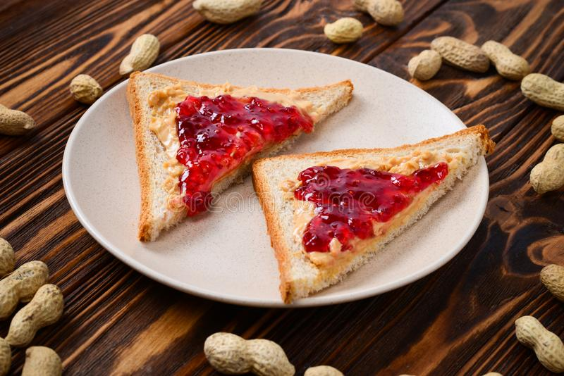 Peanut butter and jelly sandwich on wooden background royalty free stock photo
