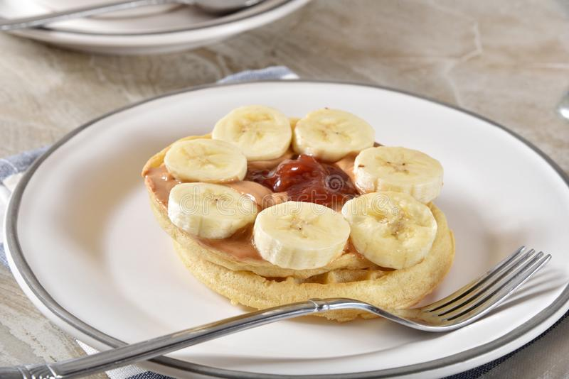 Peanut butter and jelly waffles. Delicious peanut butter and strawberry jam waffles with sliced banana royalty free stock image