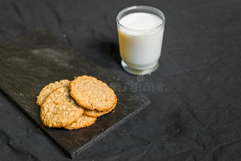 Peanut butter oatmeal cookies with milk against black background. Peanut butter oatmeal cookies with milk stock images