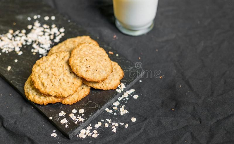 Peanut butter oatmeal cookies with milk against black background. Peanut butter oatmeal cookies with milk royalty free stock images