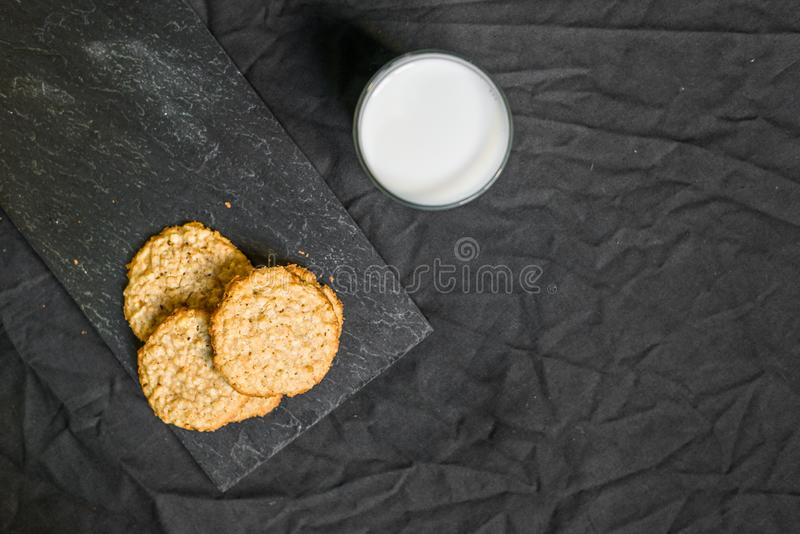 Peanut butter oatmeal cookies with milk against black background. Peanut butter oatmeal cookies with milk royalty free stock photos