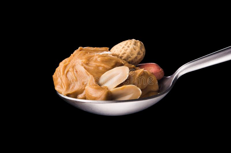 Peanut butter on a spoon. Isolated on a black background. Traditional american breakfast royalty free stock images
