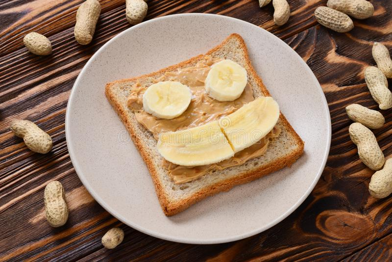 Peanut butter toast with banana slices on wooden background stock photo