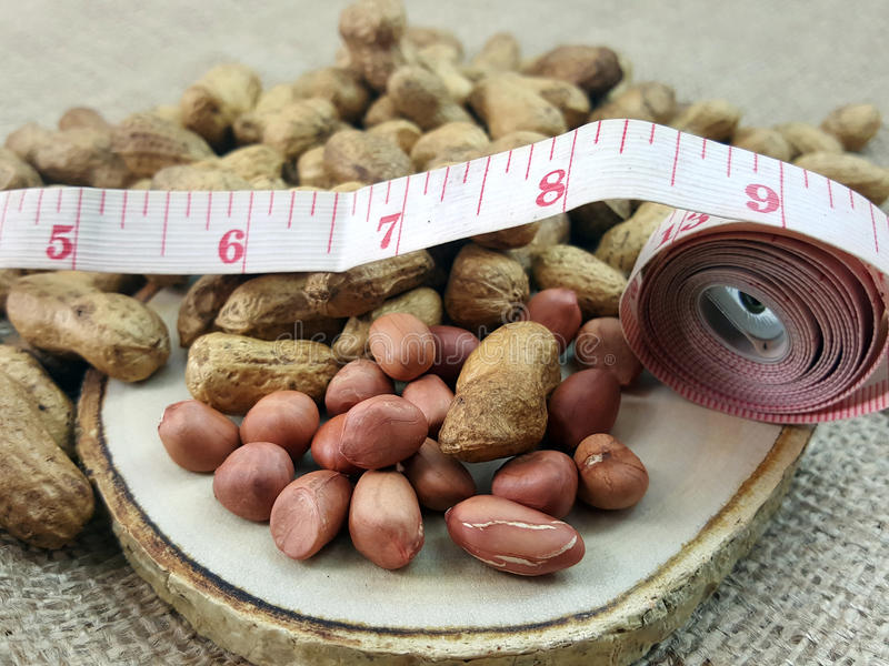 Peanut or groundnut on a wood plate with measuring tape. royalty free stock photos