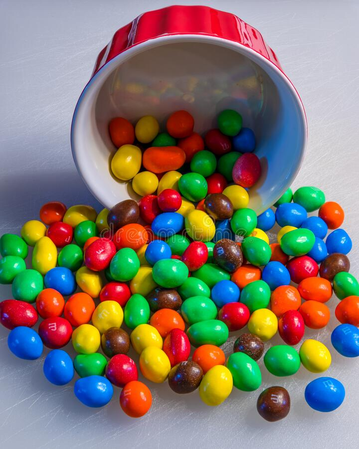Peanut M&M`s candies in a red bowl royalty free stock photo