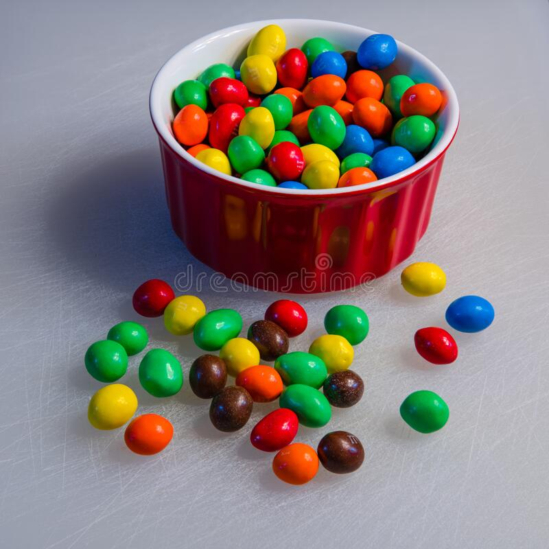 Peanut M&M`s candy in a red bowl stock photo