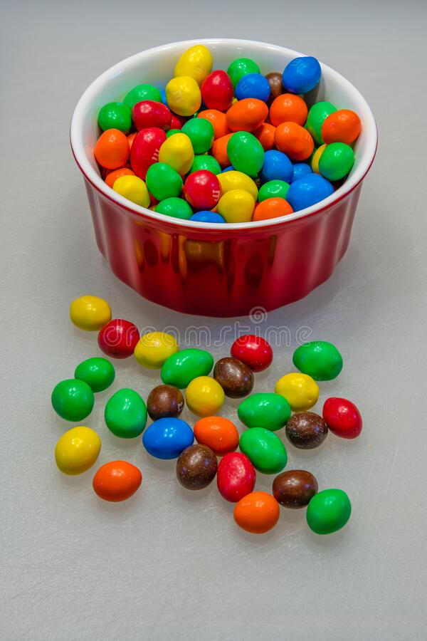 Peanut M&M`s candy in a red bowl stock images