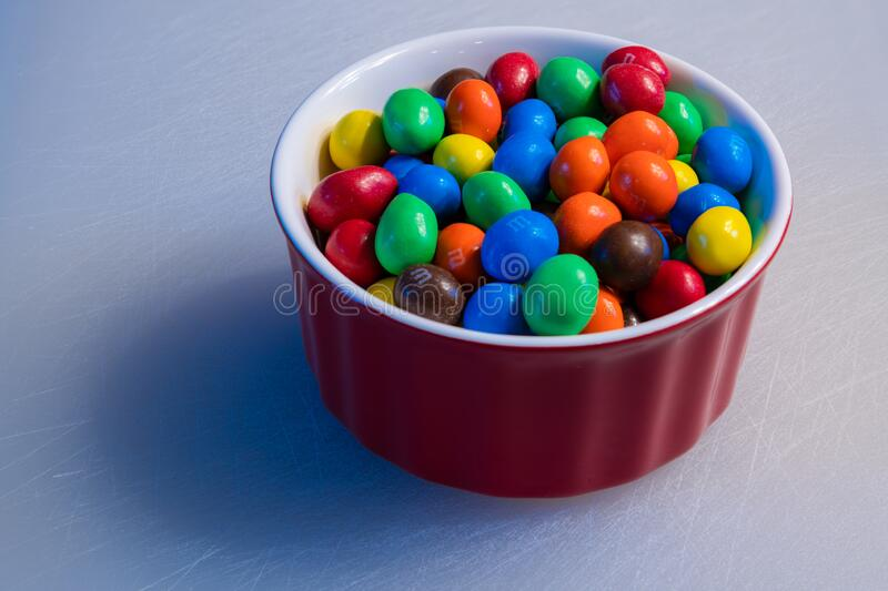 Peanut M&M`s in a colorful red bowl royalty free stock image