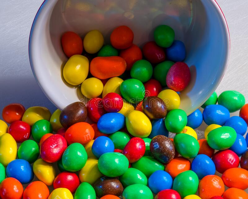 Peanut M&M`s spilling from a colorful red bowl on a white cutting board stock photos